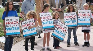 Six young children standing in a row, holding signs about fracking and water safety, at protest.